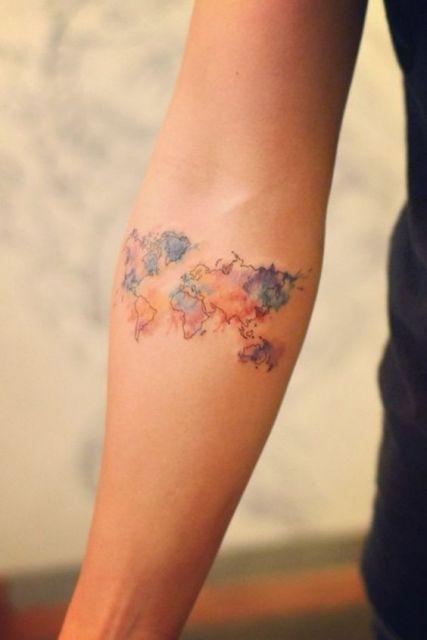 Tatuagem de mapa mundi com efeito de aquarela no antebraço