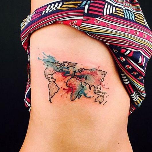 Tatuagem do mapa mundi com efeito de aquarela priorizando o vermelho e o azul nas costelas de uma mulher