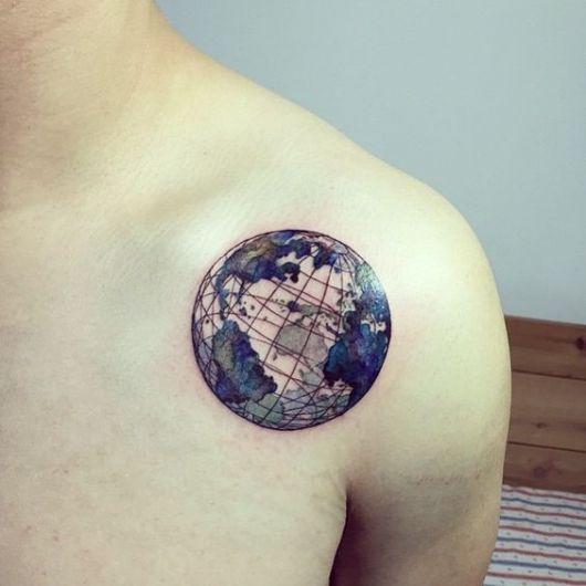 Tatuagem no ombro do Globo Terrestre pintando de azul e feito com linhas muito finas