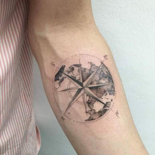 Tatuagem de uma bússola sobrepondo o Globo Terrestre no antebraço de uma pessoa