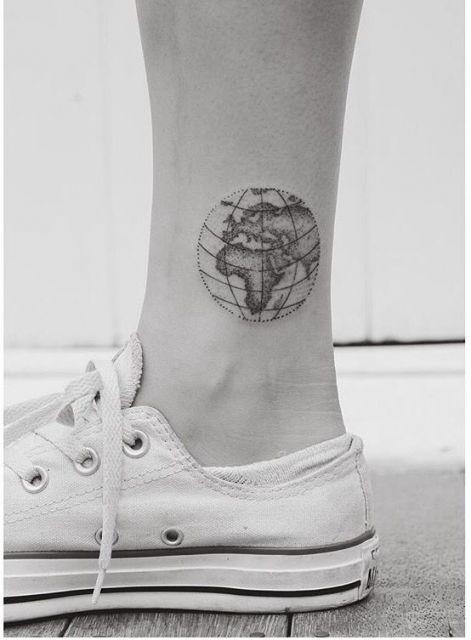 Tatuagem pequena de um Globo Terrestre com traços muito finos e um sombreamento leve