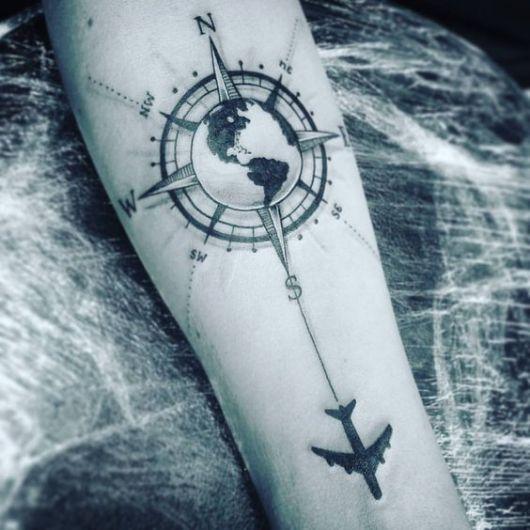 Tatuagem de uma bússola atrás do Mapa Mundi com um avião próximo