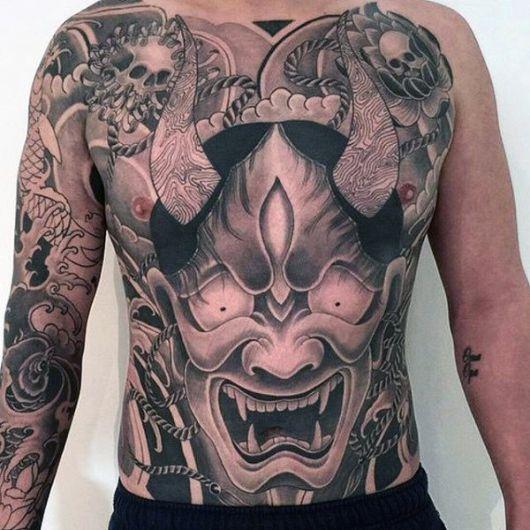 Tatuagem oriental de uma Hannya preenchendo a barriga de um homem
