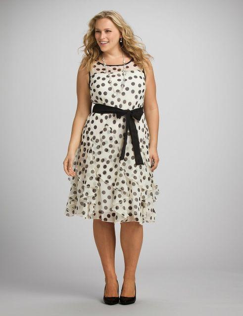 90bada282 Modelo usa vestido branco de bolinhas com faixa preta ajustada a cintura.