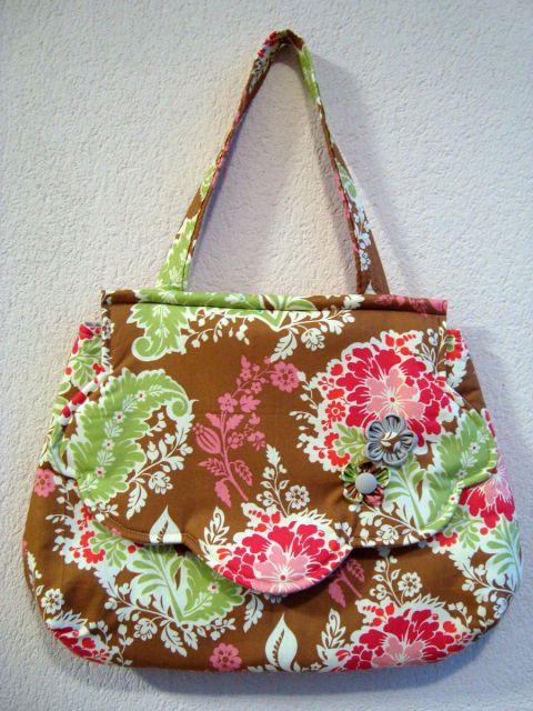 Modelo de bolsa estampada nas cores amarelo queimado, verde e rosa, com alça curta.