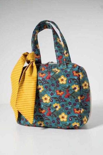 Modelo de bolsa feita em tecido na cor azul e amarelo, pequena com laço de fita amarelo.