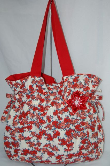 Modelo de bolsa franzida, estampada nas cores vermelho e branco, com detalhe de flor vermelha.