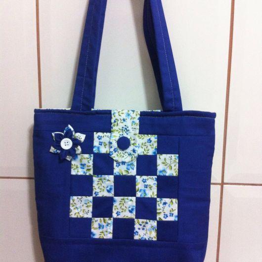 Modelo de bolsa grande na cor azul bic e estampado delicado floral azul claro e branco.