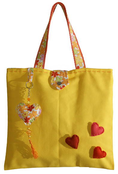 Modelo de bolsa amarela com alça estampada e detalhes de coração vermelho.