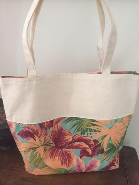 Modelo de bolsa de tecido cru com detalhe de tecido estampado em floral.