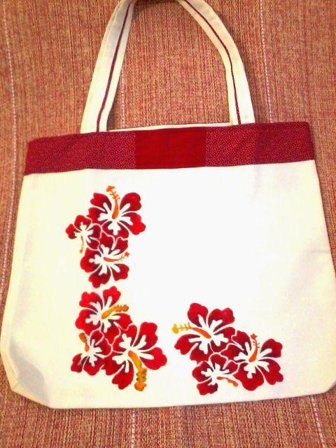 Modelo de bolsa de tecido cru, com detalhes em vermelho, de flores.