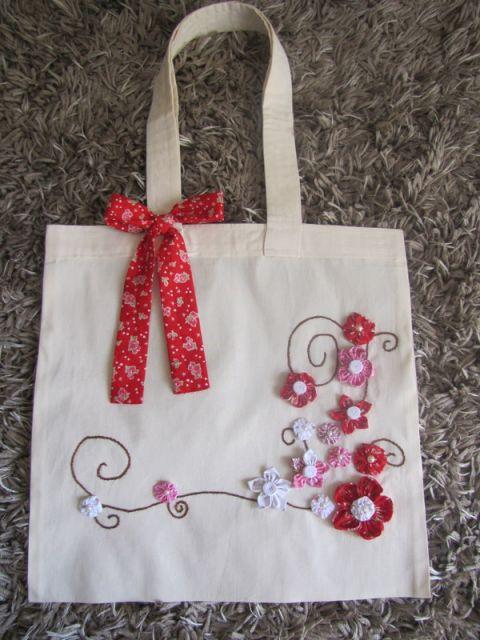 Modelo de bolsa em tecido cru, com colagens de flores rosa, branco e vermelhas e detalhe de laço.
