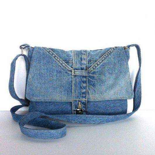 Modelo de bolsa jeans azul clara desbotada com alça longa transversal.