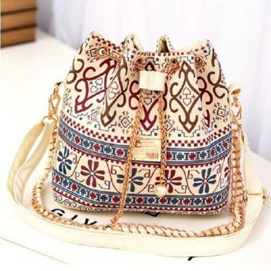 Modelo de bolsa estampada nas cores bege, azul e bordê com alça transversal longa na cor caramelo claro.
