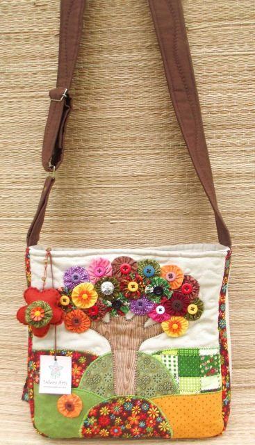 Modelo de bolsa na colorida com desenhos e colagens, com alça transversal longa marrom.