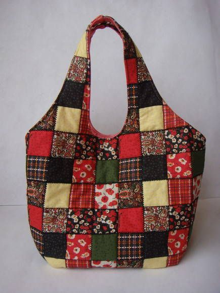 Modelo de bolsa com remendos nas cores marrom, vermelho, amarelo e verde.