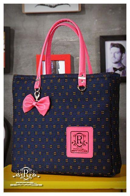Modelo de bolsa de tecido tradicional com zíper, na cor azul, com detalhe rosa de laço e na alça da peça.
