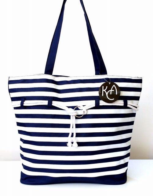 Modelo de bolsa de tecido listrada na s cores branco e azul, com alça azul escura.