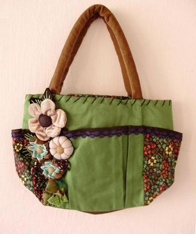 Modelo de bolsa verde, com alça marrom, bolsinhos estampados e flores.