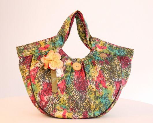 Modelo de bolsa colorida estampada, com botão e flor com detalhes em amarelo.