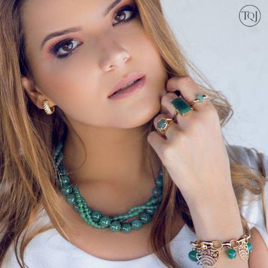 Modelo usa blusa branca, colar verde, pulseira e brincos de argola pequeno na cor dourada.