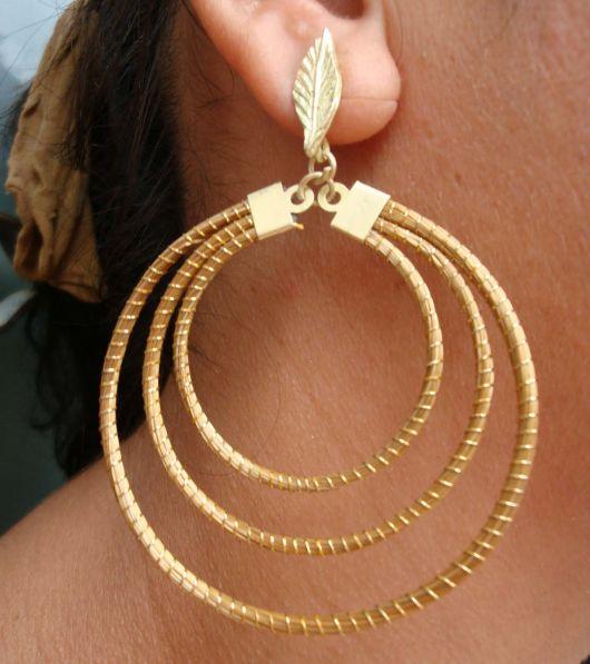 Modelo usa argola na cor ouro, com folhinha e tres em uma embutidas.