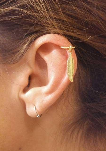 Modelo de brinco de argola para cartilagem dourado com pingente de folha.