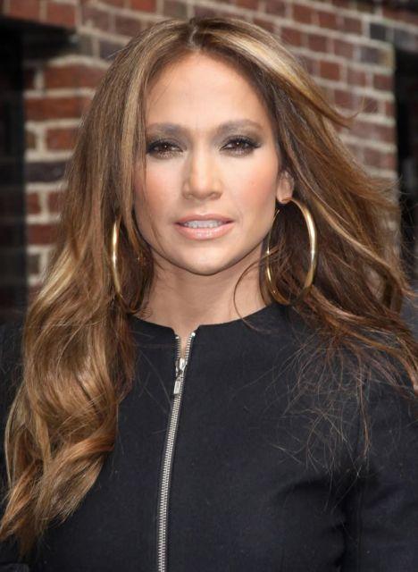 Jenifer Lopes usa blusa preta de fecho e brinco de argola grande na cor amarelo ouro.