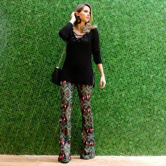 Modelo veste blusa preta meia manga compridinha, calça flare estampada nas cores vermelho e preto e verde musgo com sapato de salto e bolsa preta de alça corrente.