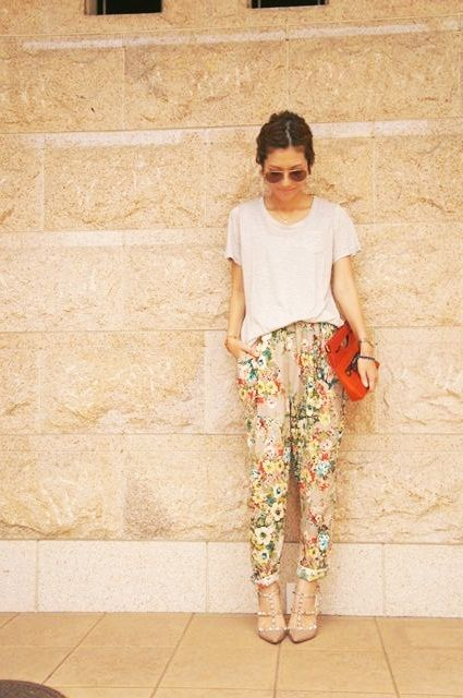 Modelo usa camisetinha v=branca, calça floral estampada na cor bege claro com sapato no mesmo tom.