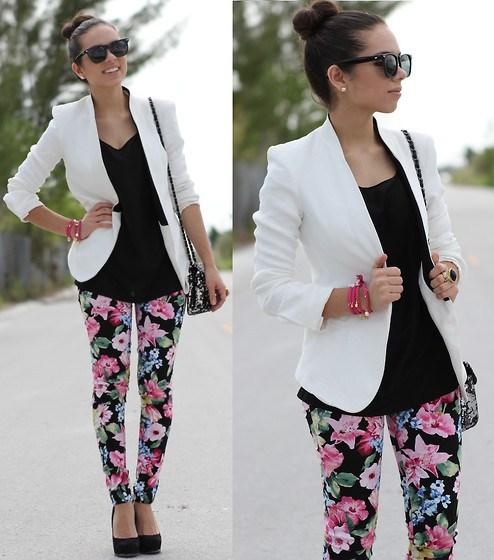 Modelo usa calça estampa floral rosa com preto, blazer branco, blusa preta e sapato preto.