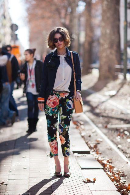 Modelo usa calça estampa floral grande, com camisa branca, jaqueta colegial, scarpin preto e bolsa alça longa marela.