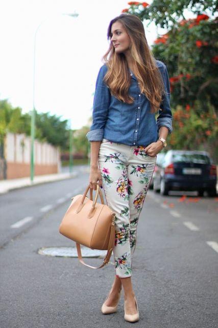Modelo veste calça branca com estampa floral, sapato nude, bolsa na mesma cor e camisa jeans azul escuro.
