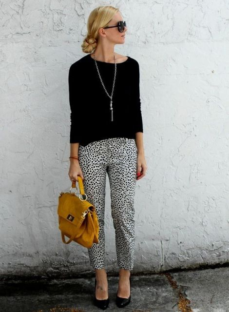 Modelo usa calça branca com estampado preto, blusa preta de linha, sapatilha e bolsa amarela de mão (alça curta).