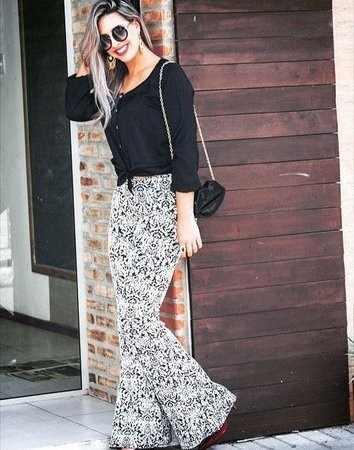Modelo veste calça branca com estampado em preto sutil, blusa preta e bolsa pequena com alça corrente comprida.