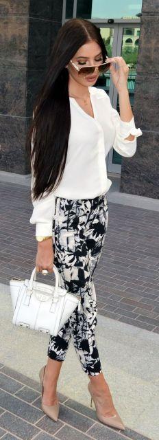 Modelo usa camisa branca, calça preta e branca estampada, bolsa branca e sapato nude.