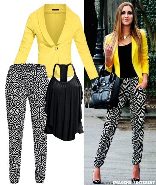 Modelo usa calça preta estampada com branco, blusa preta, scarpin e blazer amarelo.