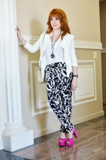 Modelo usa calça estampa preto e branco com sapato cor de rosa e blazer branco.