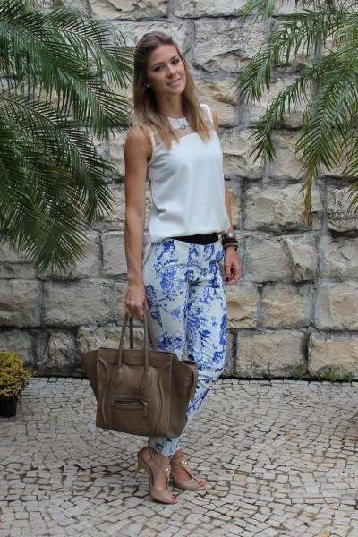 Modelo veste calça branco com estampa azul, blusa branca, sapato nude, bolsa marrom.