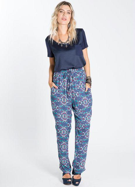 Modelo usa calça azul estampada, blusa azul de cetim e sapato de salto preto.