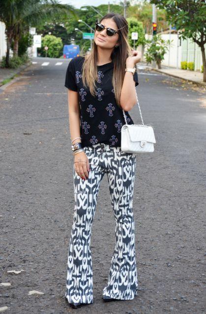 Modelo usa calça estampada branca com azul, bolsa branca e blusa preta.