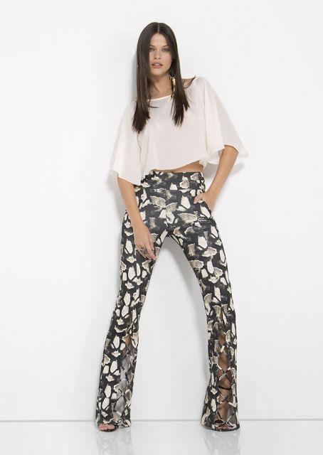 Modelo usa calça estampada blusa branca cropped de manguinhas e sapato de salto.
