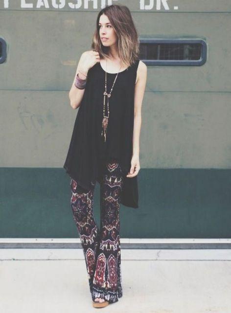 Modelo usa calça estampada escura, sapato de salto e blusa preta de alcinhas.