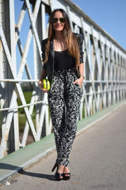 Modelo usa blusa, jaqueta e sapato preto com calça estampada em preto e cinza com bolsa verde e amarelo (clutch).