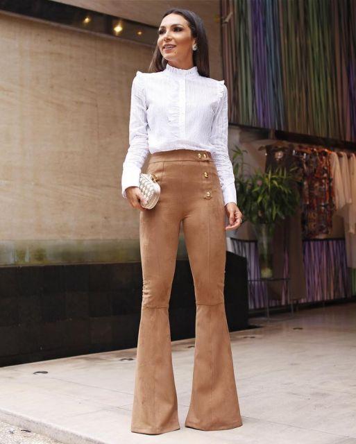 Modelo usa calça flare marrom com camisa branca pra dentro da calça e bolsa branca carteira de mão.