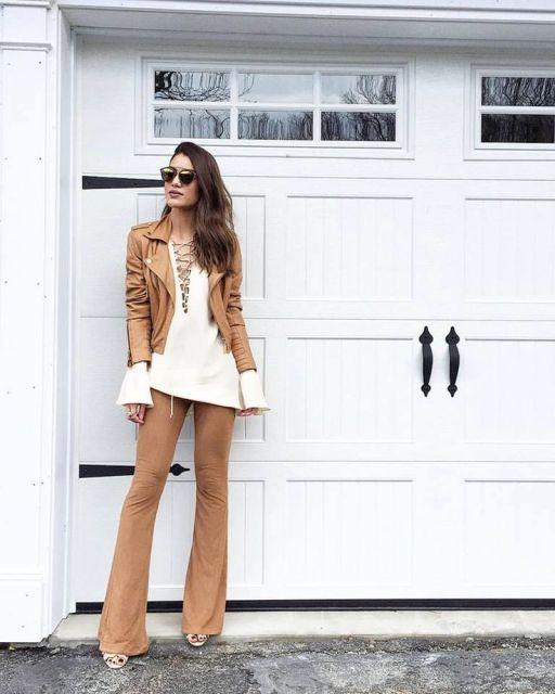 Camila Coelho usa calça suede, blusa branca larguinha e jaqueta de couroi tons terrosos.