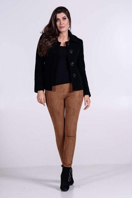 Modelo usa calça suede marrom, blusa, blazer e botinha preta.