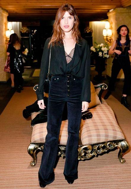 Modelo usa calça suede cintura alta preta, blusa preta larguinha de decote e bolsa no mesmo tom.