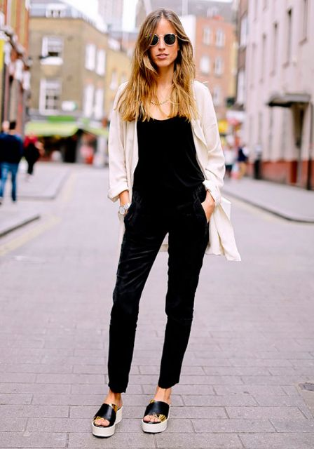 Modelo usa calça suede preta, blusa preta, casaquinho branco e chinelinho preto e branco tira larga.