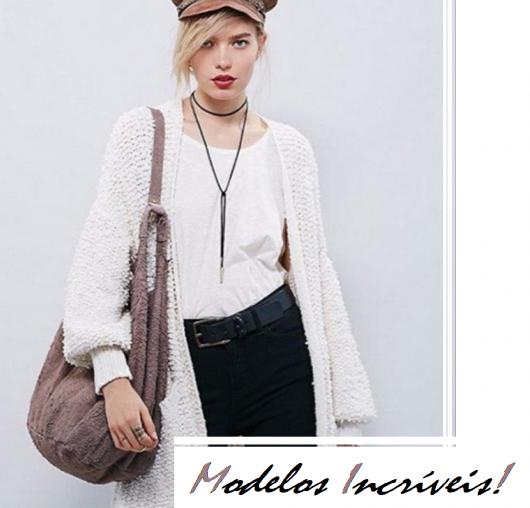 Modelo usa blusa branca, bolsa cinza, colar de couro preto, casaquinho branco, calça preta e boina caramelo.